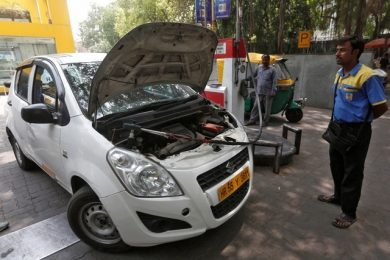Gas station attendant stands next to a vehicle as he fills it with CNG in New Delhi