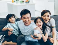 Cheerful asian family watching tv together